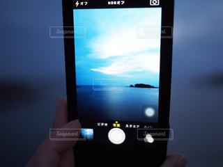 携帯電話の画面にテキストを持っている手の写真・画像素材[781074]