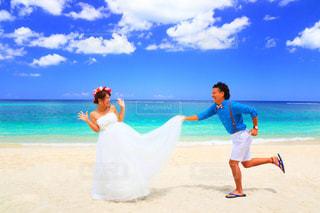 海の横にある砂浜のビーチの上に立っている人 - No.984066