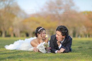 草の中に座っている人々 のカップルの写真・画像素材[1210438]