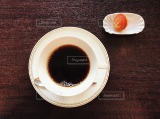 テーブルの上のコーヒー カップと一口菓子の写真・画像素材[1030845]