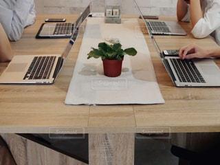 木製テーブルの上に座っているラップトップ コンピューターを使用している人の写真・画像素材[1328889]