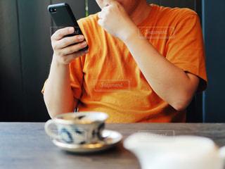 携帯電話を見てテーブルに座っている男の人の写真・画像素材[1367491]