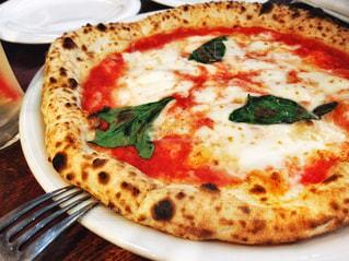 白い板の上に座ってピザの写真・画像素材[1381033]