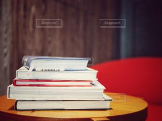 木製テーブルの上に座っている本の山の写真・画像素材[1381042]