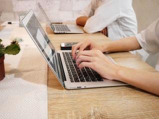 木製テーブルの上に座っているラップトップ コンピューターを使用している人の写真・画像素材[1522108]