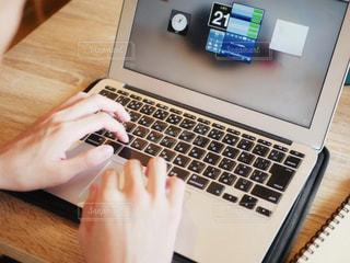 木製テーブルの上に座っているラップトップ コンピューターを使用している人の写真・画像素材[1522110]