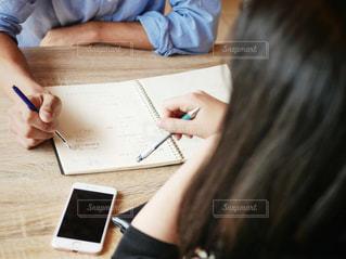 ラップトップを使用してテーブルに座っている人の写真・画像素材[1544393]