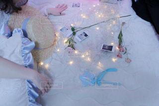 ベッドの上でチェキフィルムを眺める女性の写真・画像素材[1653101]