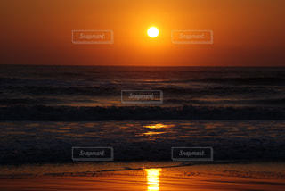 海の横にあるビーチに沈む夕日の写真・画像素材[719869]