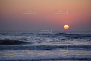海の横にあるビーチに沈む夕日の写真・画像素材[719870]