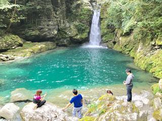 水の横にある岩の上の人々 のグループの写真・画像素材[763526]