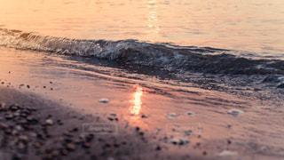 夕暮れ時のビーチの波打ち際の写真・画像素材[1111697]