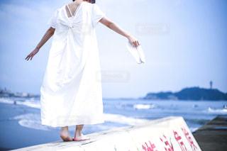 堤防を歩く白いワンピースの女の子の写真・画像素材[3187568]