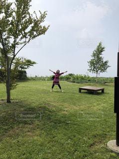 芝生のフィールドでフリスビーを投げる男の写真・画像素材[1330237]