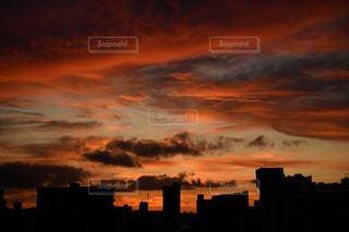都会と曇りの空に沈む夕日の写真・画像素材[2384882]