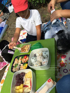 食物と一緒にテーブルに座っている人々 のグループの写真・画像素材[813728]