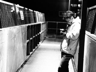 フェンスの横に立っている人の写真・画像素材[731062]