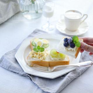 食品やコーヒー テーブルの上のカップのプレートの写真・画像素材[1449573]