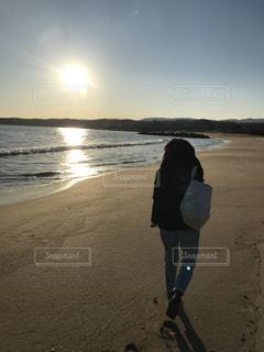 水の体の横にビーチの上を歩く男 - No.959244