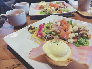 食品やコーヒー テーブルの上のカップのプレートの写真・画像素材[957089]