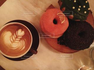 近くのコーヒー カップの横に座っているドーナツのアップの写真・画像素材[1013057]
