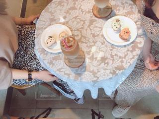 食べ物の皿を持ってテーブルに座っている人の写真・画像素材[2411182]