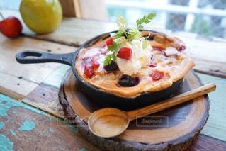 木製のテーブルの上に座っている食べ物のボウルの写真・画像素材[2692128]