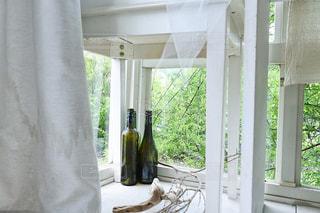 ボトルと緑が見える窓の写真・画像素材[1232587]