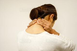 首が痛くて手で押さえる女性の写真・画像素材[2334244]