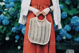 赤いワンピースとかごバッグの写真・画像素材[1288754]