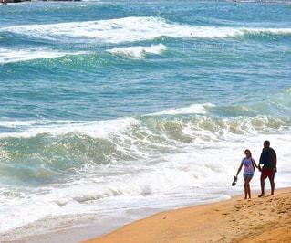 ビーチを散歩するカップルの写真・画像素材[718618]