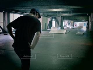 暗い部屋に立っている男の写真・画像素材[713848]
