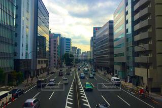 背の高い建物に囲まれたトラフィックでいっぱい街の通りのビューの写真・画像素材[812162]