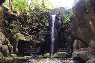 岩が多い崖の上の大きな滝の写真・画像素材[1048847]