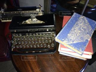 テーブルの上のタイプライターと本の写真・画像素材[915639]