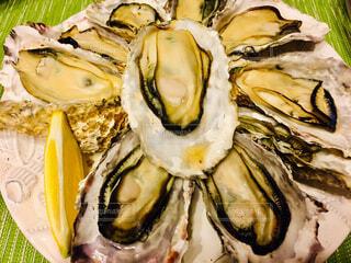 レモンとたくさんの焼き牡蠣のクローズアップの写真・画像素材[4370662]