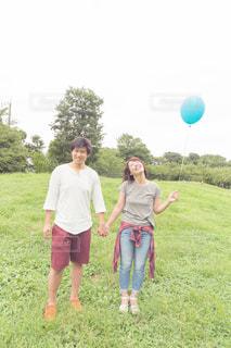 草の覆われてフィールド上に立って人々 のグループの写真・画像素材[887058]