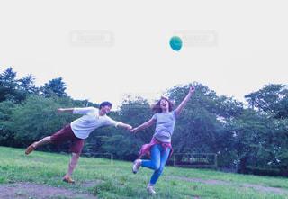 風船に引っ張られる楽しそうなカップルの写真・画像素材[887059]