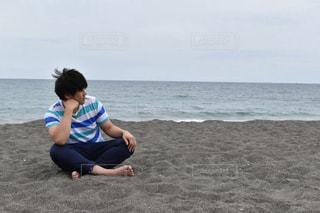 ビーチに座っている少年の写真・画像素材[887090]