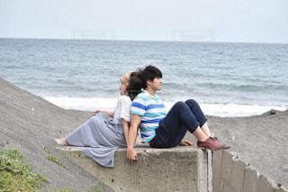 砂浜で背中合わせに座るカップルの写真・画像素材[887100]