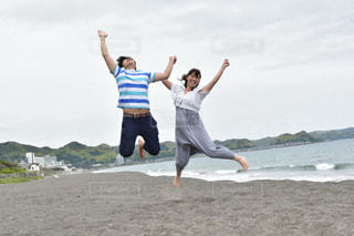 浜辺でジャンプするカップルの写真・画像素材[887104]