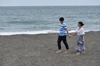 海岸で手を繋ぐカップルの写真・画像素材[887110]