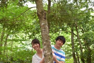 木の間から顔を出すカップルの写真・画像素材[887120]