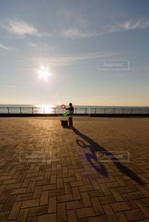 海に沈む夕日とピエロのジャグリングの写真・画像素材[930221]