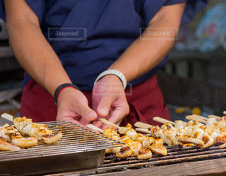 イカ串焼き焼いてる人の写真・画像素材[930325]