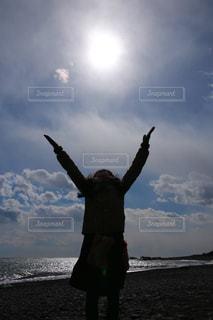 空に向かって手を広げる 逆光の写真・画像素材[989183]
