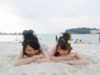 水の体の近くのビーチに座っている女性 - No.754945
