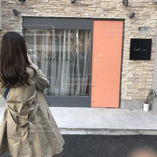 携帯電話で話している建物の前に立っている女性 - No.1111789