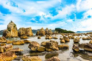 海の近くの岩の上に座っている人々 のグループ - No.806882