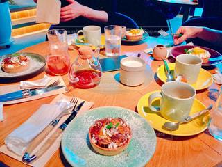 食品のプレートをテーブルに座っている女性 - No.935920